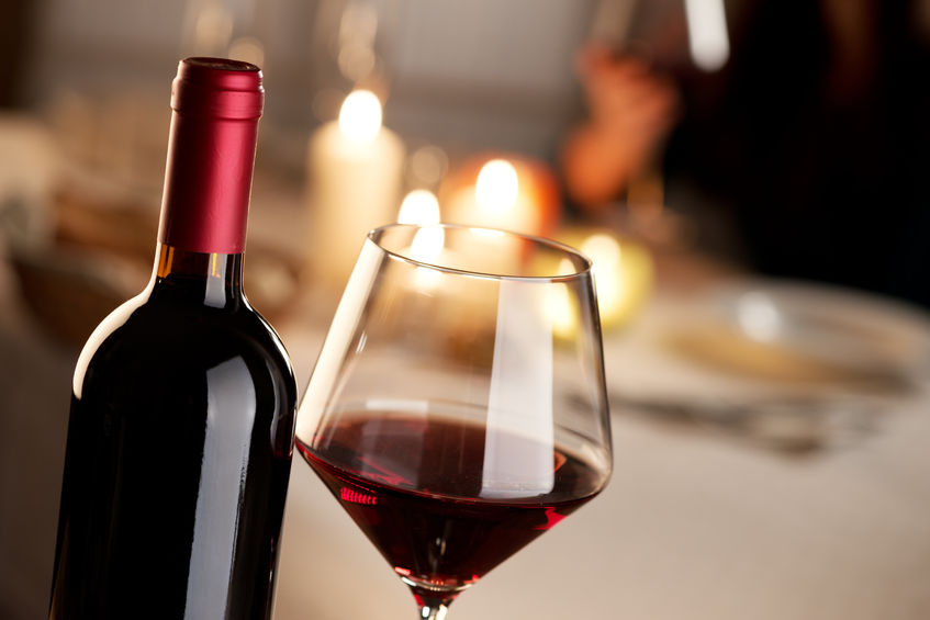 bottle and glass of red wine with restaurant on background.